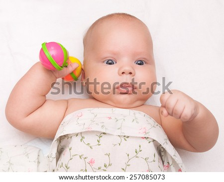 baby boy playing with rattle. charming child lying on back. children's toys. family concept. white background. few month old infant. newborn. close up portrait of kid.  - stock photo