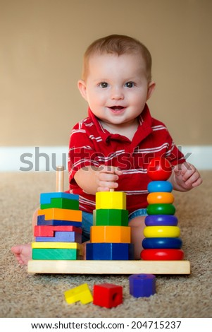 Baby boy playing with stacking learning toy - stock photo