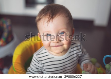 Baby boy portrait on the baby walker at home - stock photo