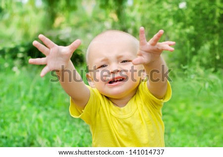 Baby boy reaching towards the viewer in park - stock photo