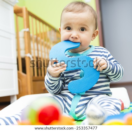 Baby boy sitting and having fun in his room  - stock photo