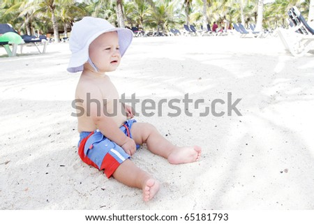 Baby boy sitting on beach, playing in sand - stock photo