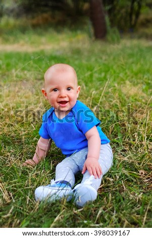 Baby boy sitting on green grass. Beautiful happy little child sitting on a meadow on the nature in the park. Portrait of laughing and smiling cute baby kid. - stock photo