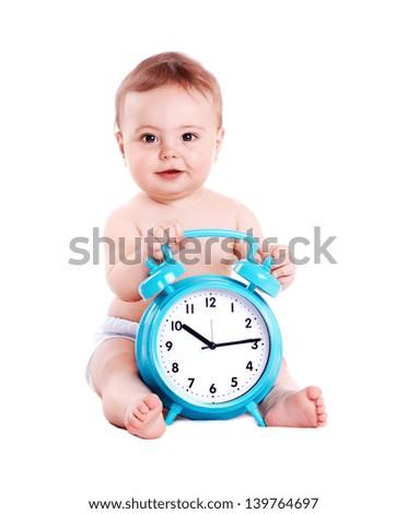 Baby boy sitting on white background holding the big blue alarm clock - stock photo