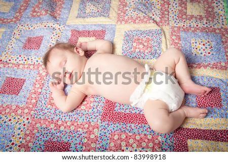 Baby boy sleeping on back on blanket - stock photo