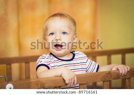 Baby boy standing in a cot - stock photo