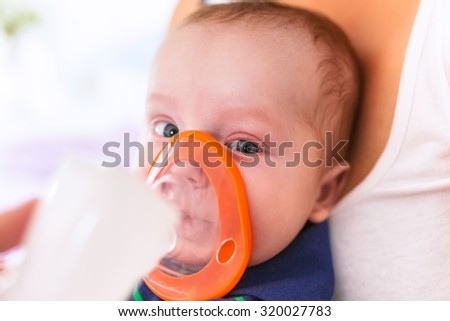 Baby boy taking inhalation therapy by the mask of a nebuliser - stock photo