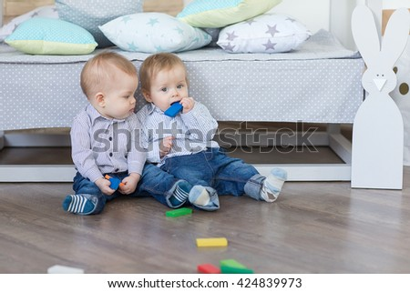 Baby boy twins playing with the toy wooden cubes and dice - stock photo