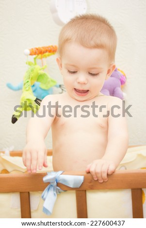 Baby boy waving hand and standing up in crib - stock photo