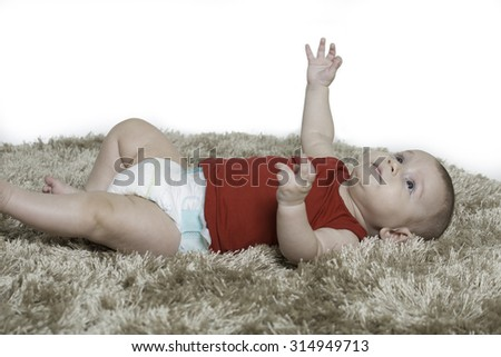 baby boy wearing a diaper lying on his back on a brown carpet ,raising his right hand up, looking up - stock photo
