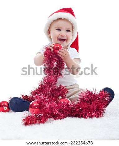 Baby boy wearing santa hat holding christmas ornaments - stock photo