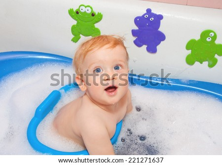 Baby boy with blue eyes in bath with toys - stock photo