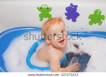 Baby boy with blue eyes in bath with toys plays with water - stock photo
