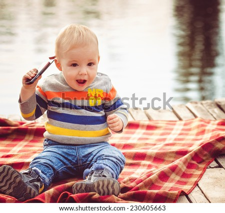 Baby boy with cell phone outdoors - stock photo
