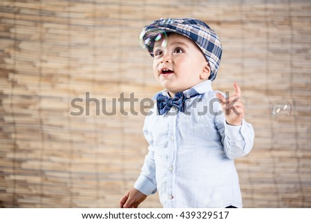 baby boy with gentleman outfit on bamboo background - stock photo