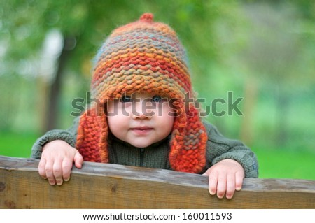 Baby boy with knitted hat, outdoors - stock photo