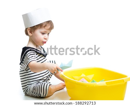 baby boy with sailor hat  playing with paper boats - stock photo