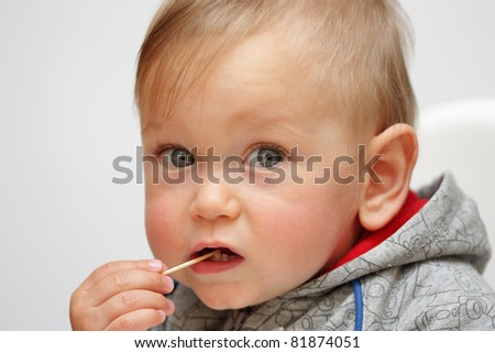 Baby boy with toothpick in mouth - stock photo