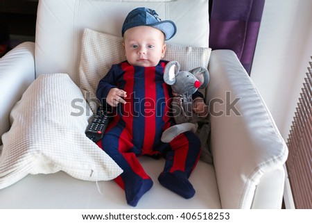 Baby boy with TV remote control on the couch - stock photo