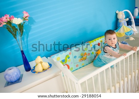 Baby boy ( 1 year old ) playing in baby bed at children's room. - stock photo