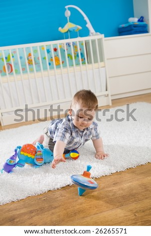 Baby boy ( 1 year old ) sitting on floor at home and playing with whirligig. - stock photo