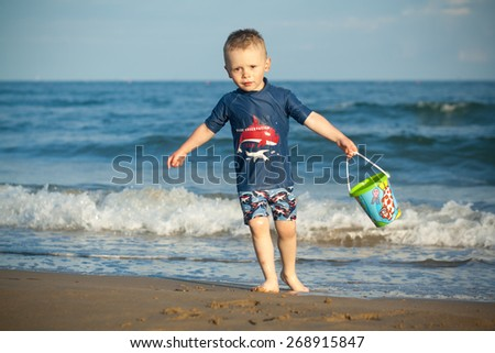 baby boy 3 years old by the sea playing with water and kid's pail, sea with waves background, Italy - stock photo