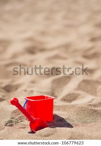 Baby bucket and shovel on the sandy beach - stock photo