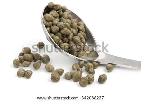 baby capers in stainless spoon isolated on white background - stock photo