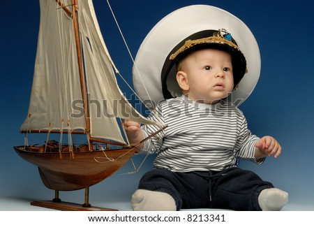 Baby captain in a cap sitting next to sail boat looking up - stock photo
