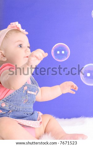 baby catching bubbles - stock photo