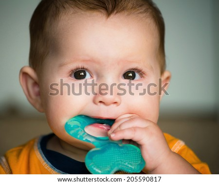Baby chewing on teething ring toy - stock photo