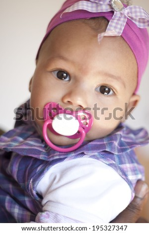 Baby Child  holding a pacifier in her mouth - stock photo