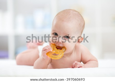 baby child lying on belly weared diaper with teether - stock photo