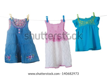 Baby clothes drying on a rope isolated on white background - stock photo