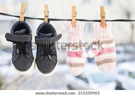 Baby clothes, gloves and shoes, hanging on the clothesline. - stock photo