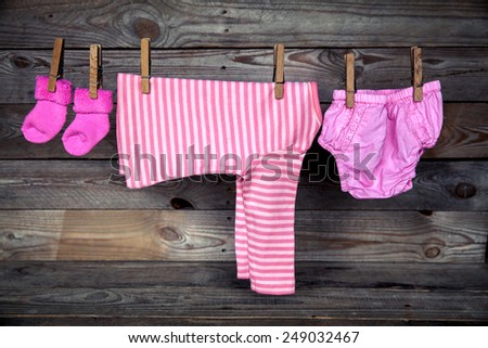 Baby clothes hanging on clothesline, on wooden background - stock photo