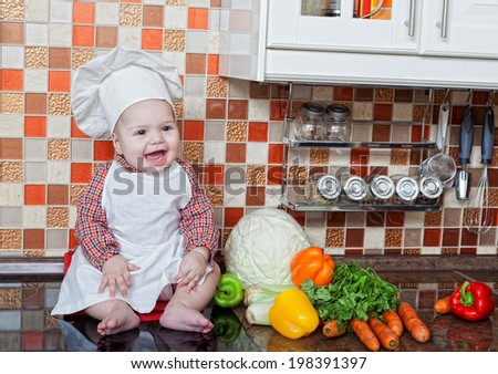 Baby cook with vegetables sits on a kitchen table - stock photo