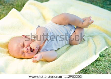 Baby crying  in a yellow towel in grass - stock photo