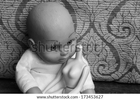 Baby doll with broken toy sit on chair - stock photo