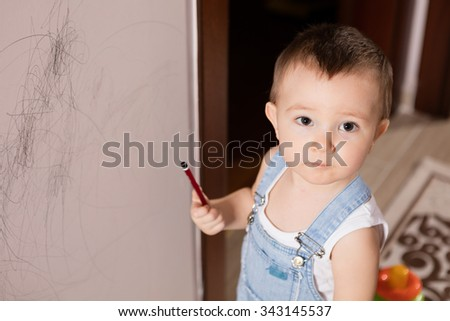 Baby drawing on wall. - stock photo