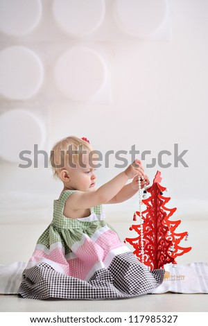 Baby dresses red Christmas tree. Christmas. A small child sitting on the floor and play. Light background. The girl in the dress. - stock photo