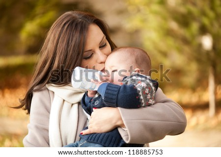 baby drinking milk in a bottle in the park - stock photo