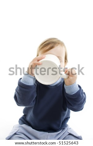 Baby drinking with big cup, studio shoot. - stock photo