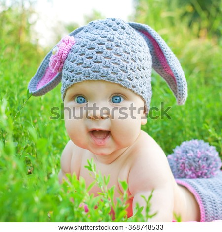 Baby Easter bunny in the spring green grass. Easter holiday concept - stock photo