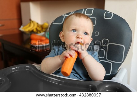 Baby eating carrot in a chair - stock photo
