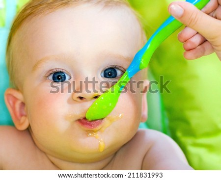 Baby eating first food in spoon. Happy newborn baby boy with straight fair hair and blue eyes tasting green spoon full of food. - stock photo