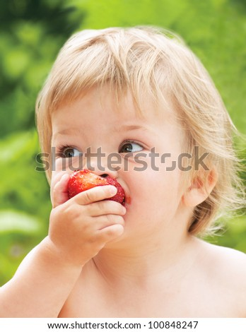 Baby eating strawberry - stock photo
