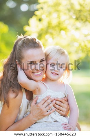 Baby embracing mother outdoors - stock photo