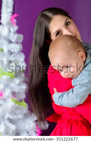 baby falls asleep on her mother's shoulder on Christmas night - stock photo