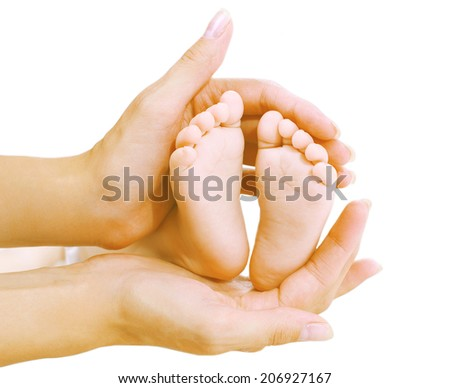 Baby feet in hands mother - stock photo